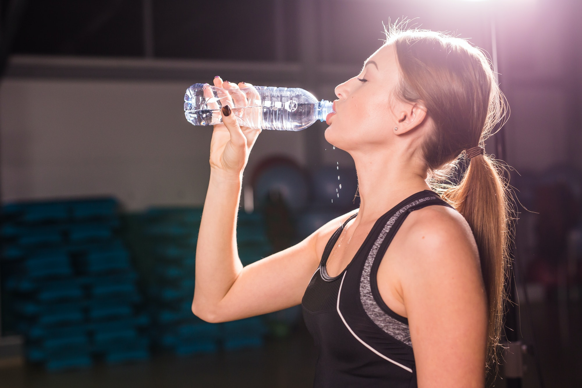 Beautiful fitness woman drinking water from the bottle